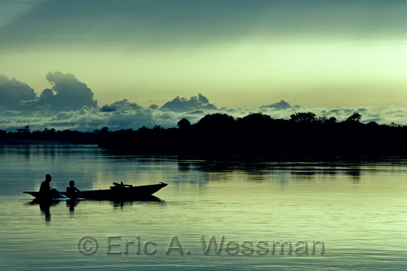 Sunset Silhouette of people in boat (dugout canoe) on water. Zaire River, Zaire. (Congo River, Democratic Republic of Congo)