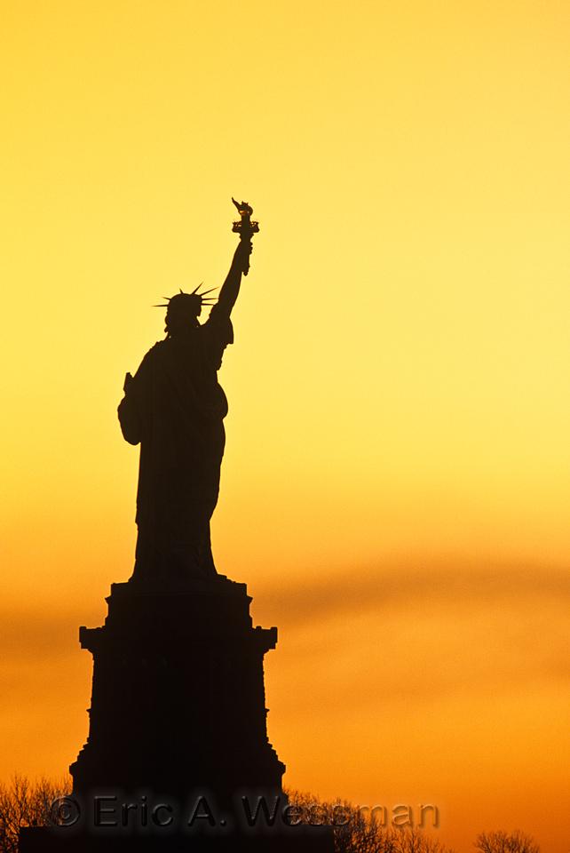 Statue of Liberty at sunrise. New York Harbor, New York.