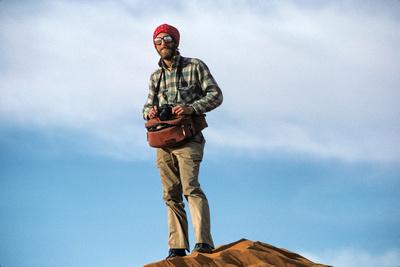 Travel photographer Eric A. Wessman on a sand dune in Tiguentourine, Algeria, in the Sahara Desert.